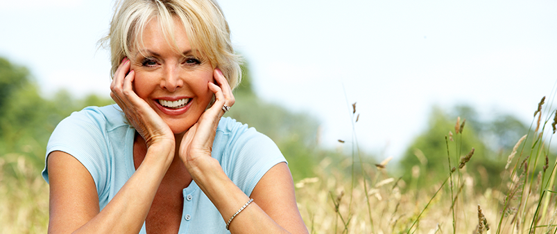 A middle-aged woman smiling outdoors
